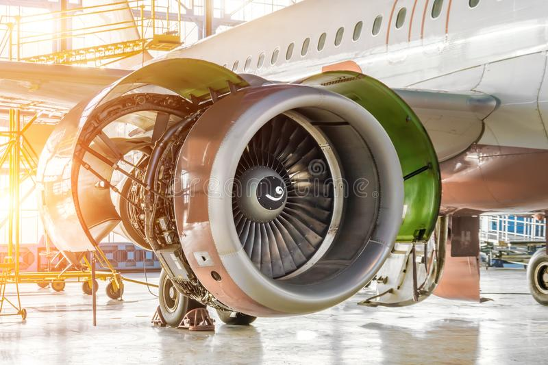 Opened hood aircraft engine jet under maintenance in the hangar stock photography