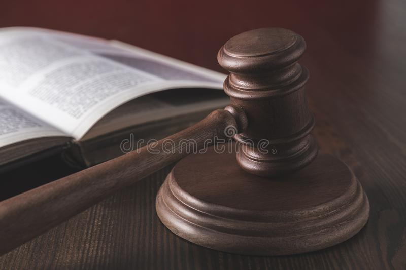 Opened juridical book with hammer on wooden table,. Law concept stock images