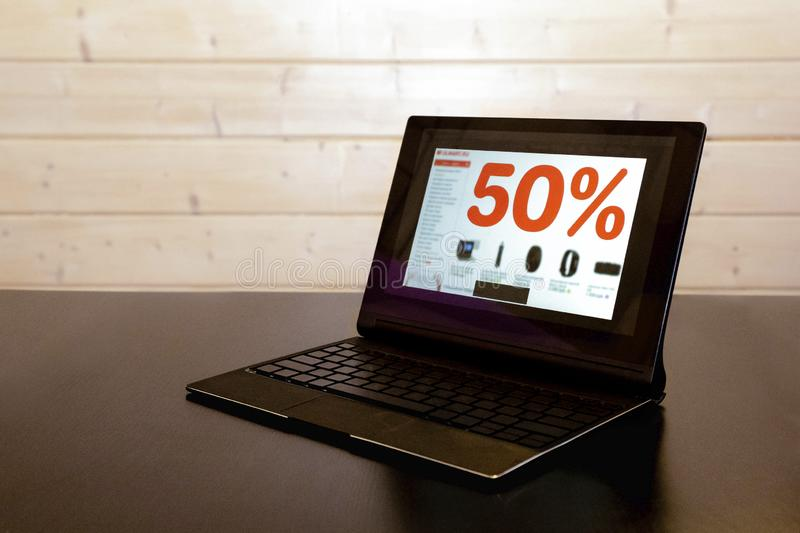 Opened laptop, computers on screen where inscription - sale in online store, 50% discount. Promotion E-commerce Shop.  royalty free stock photos