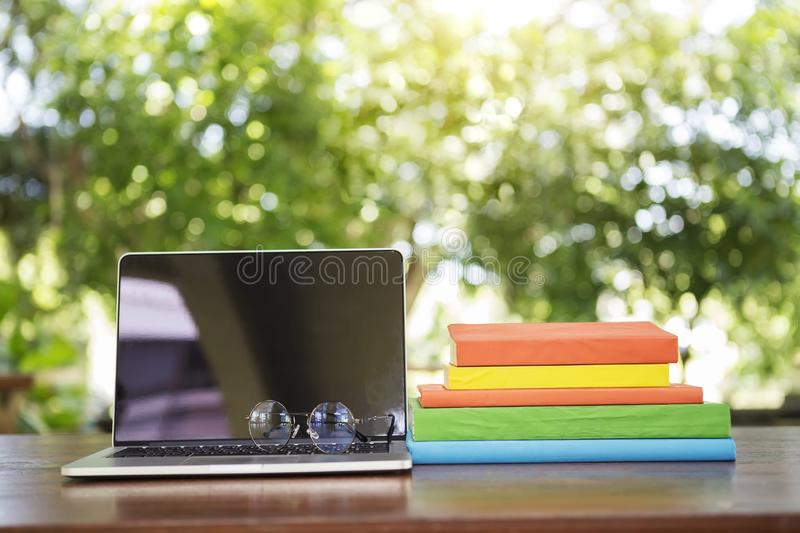 Opened laptop with glasses and books stacked on wood table with stock photos