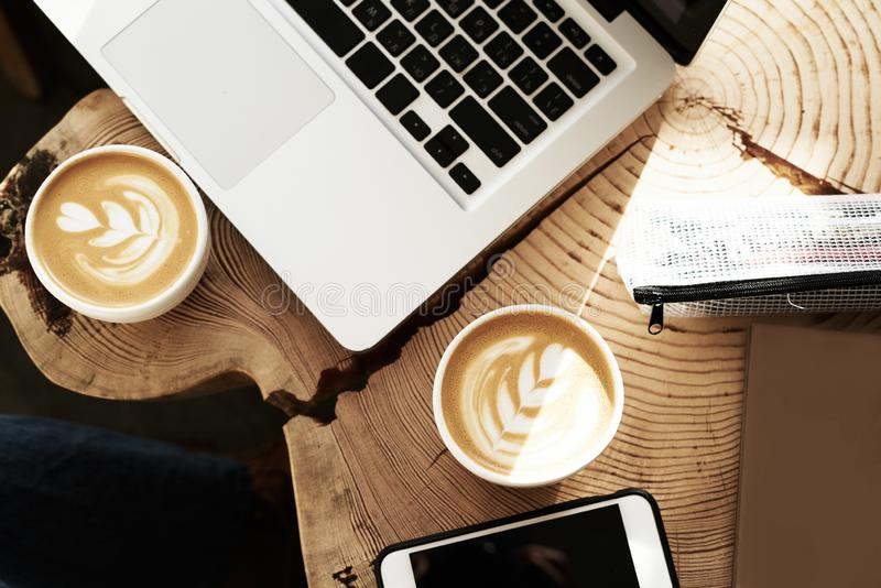 Opened laptop and two cup of coffee with flower decoration on top, view from above, wooden slab table.  stock photos