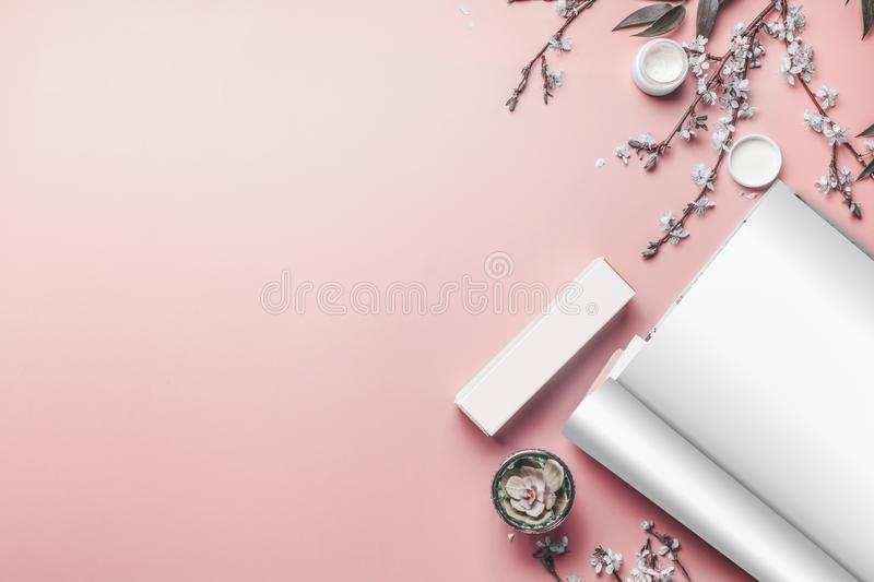 Opened magazine with blank sheets with mock up of skin care products, succulent plant and spring blossom on coral background, top stock photo