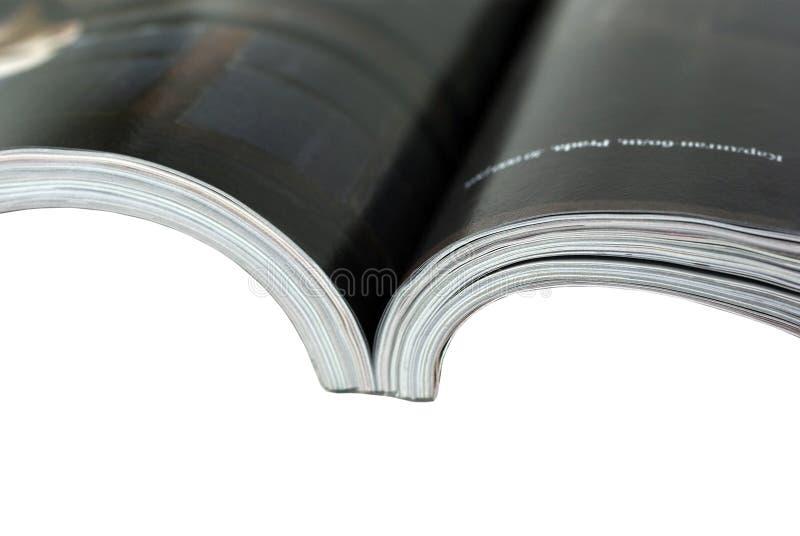 Opened magazine close-up on white background.