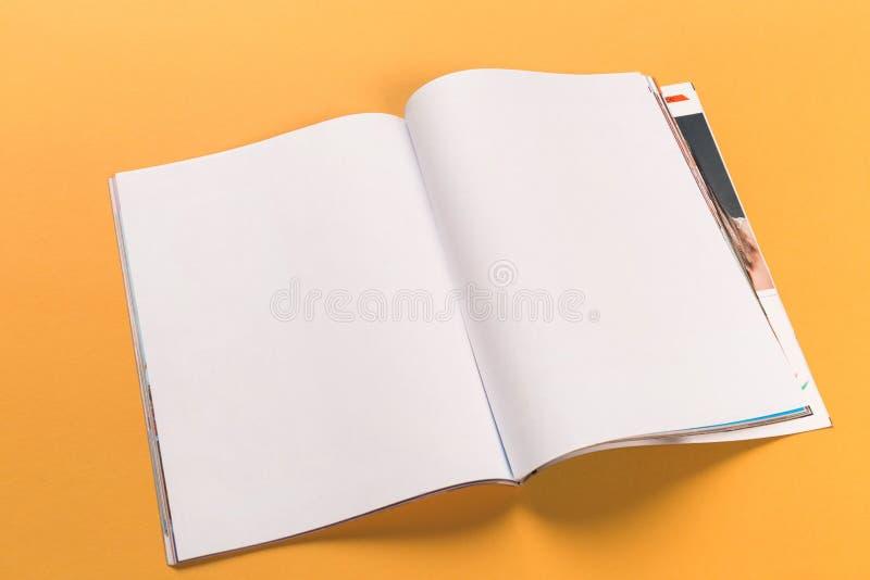 Opened magazine mock-up on orange background royalty free stock photos