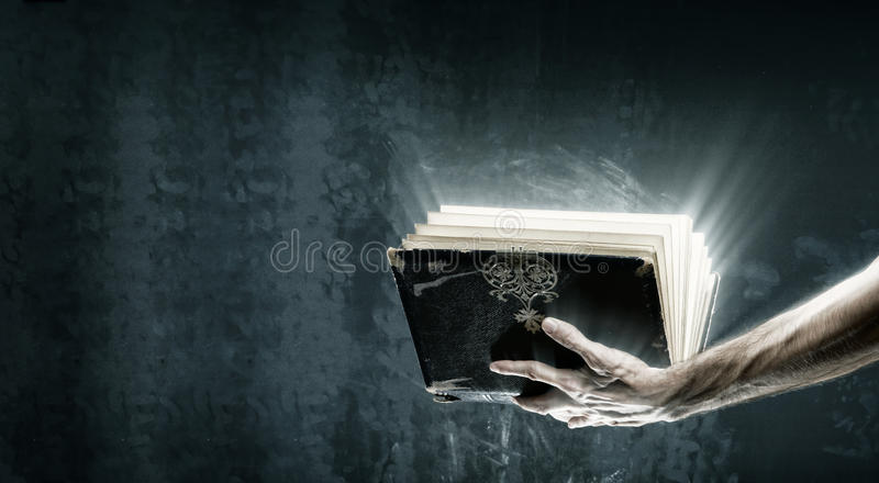 Opened magic book with magic lights. Holding magic book with magic lights stock photos