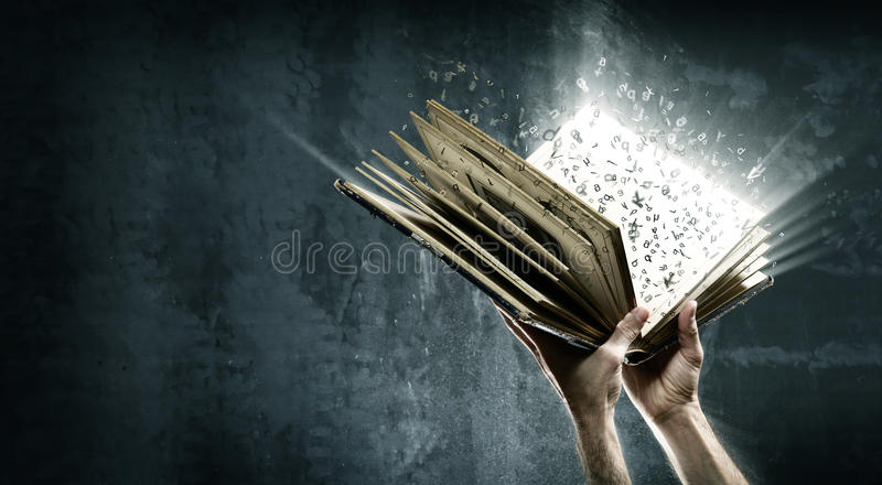 Opened magic book with magic lights. Holding magic book with flying letters stock photography
