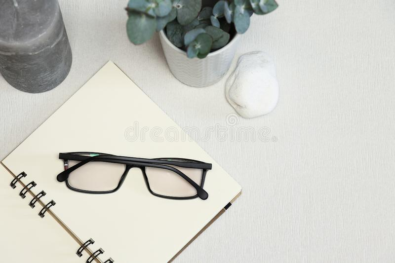 Opened notebook with dark spectacles, eucalyptus branches, stone and candle on the white background stock images
