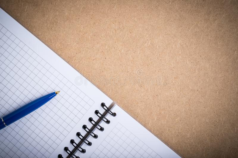 Opened Notebook With Grid Pages And Pen On Board With Copyspace. stock photo