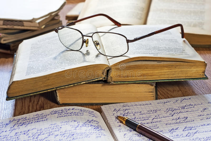 Opened notebook, pen, books and glasses royalty free stock photography