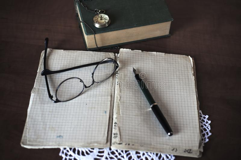 Opened notebook, pen, books and glasses stock photos