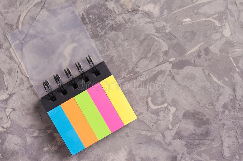 Opened notebook with spiral and blank colored pages on old concrete gray cement with copy space royalty free stock photography