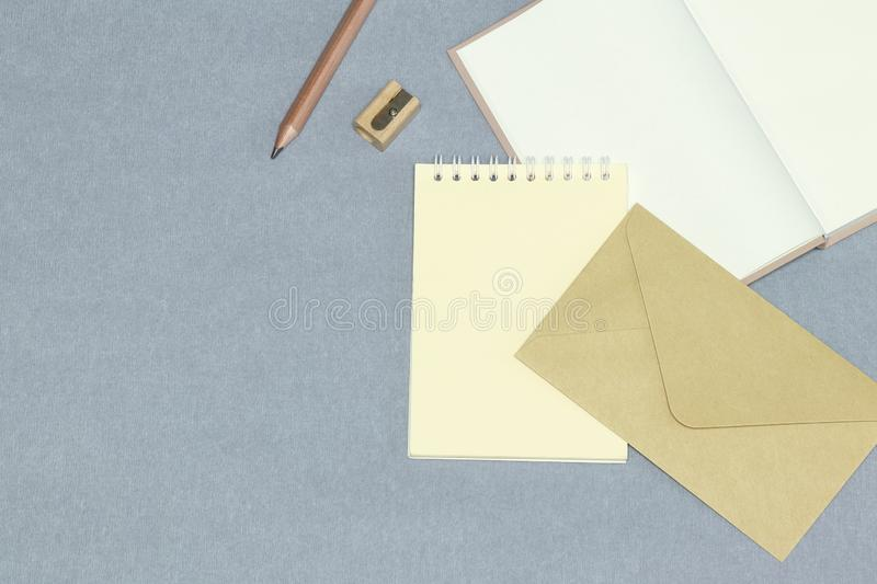 The opened notebook, envelope, wooden pencil & sharpener on the grey background stock image