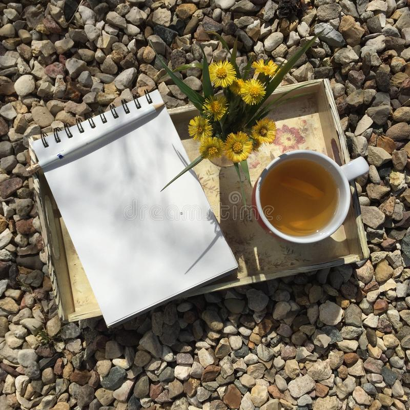 Opened notepad, pencil, tea cup and small bouquet of wild flowers on a handemade tray. Opened notepad, pencil, cup and small bouquet of wild flowers on a royalty free stock photos