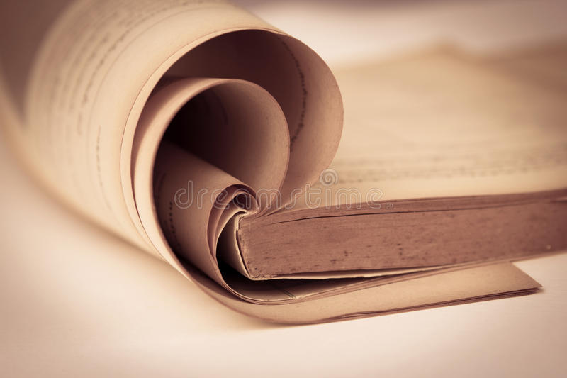 Opened old book in sepia and vintage color tone , selective focus. Opened old book in sepia and vintage color tone stock photos