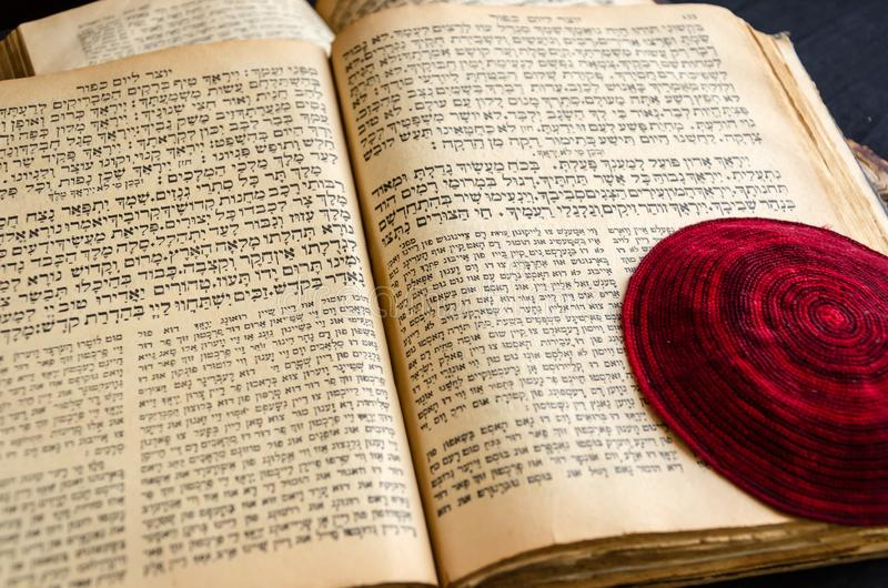 Opened old Jewish Bible. Red knitted jewish bale lies on an open scripture page. Selective focus. Closeup of hebrew text royalty free stock photography
