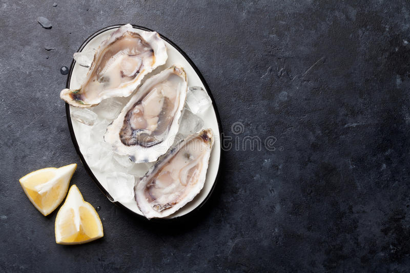 Opened oysters and lemon stock image