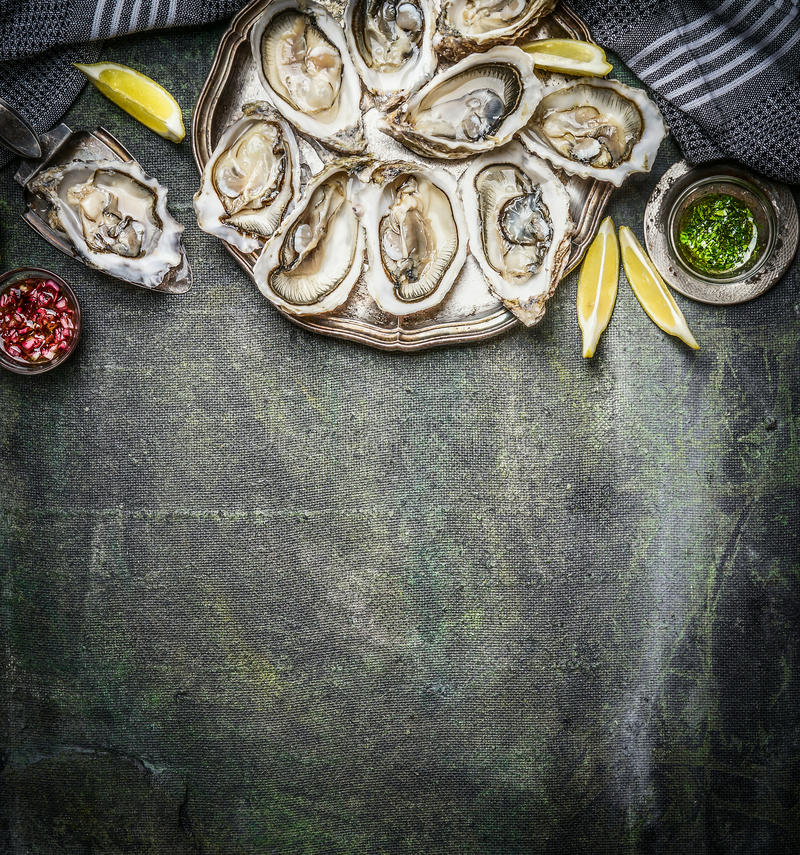 Opened oysters with lemon and various sauces on rustic background, top view royalty free stock photo