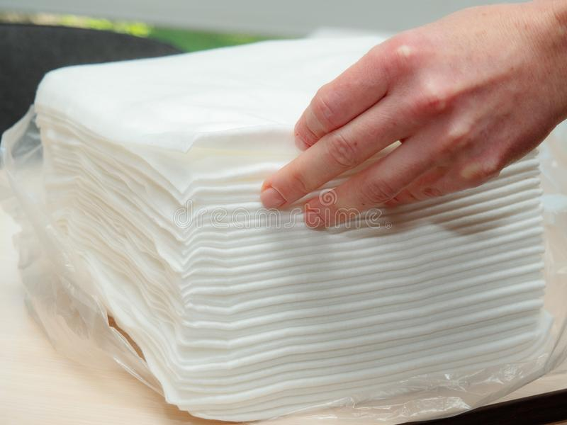 Opened pack of white paper napkins and females hand touching napkins, close up view. Stack of paper towels on table. White hygienic napkins. Selective soft stock photography
