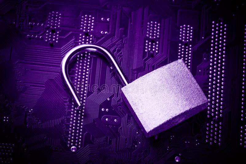 Opened padlock on computer motherboard. Internet data privacy information security concept. Ultraviolet toned image.