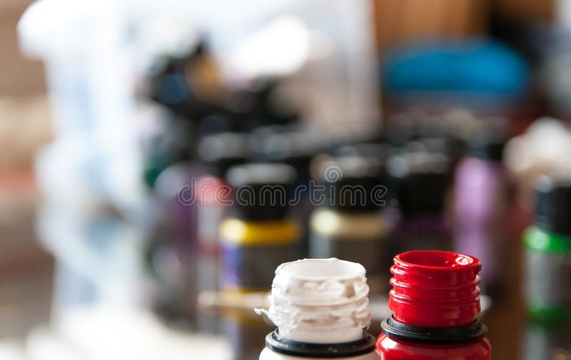 Opened paint bottles,blured background stock photo