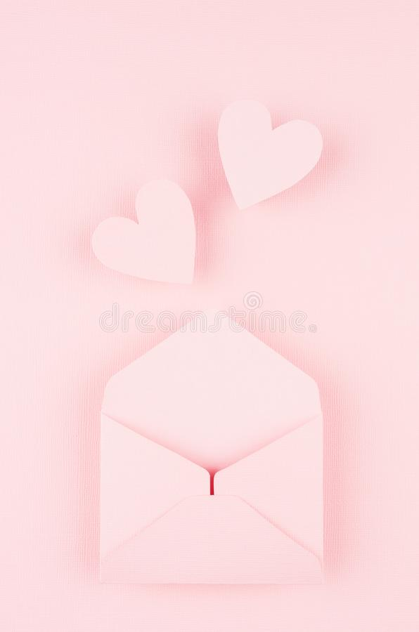 Opened paper envelope with fly out hearts on soft pink color background. Valentine day concept for design. Opened paper envelope with fly out hearts on soft royalty free stock photos