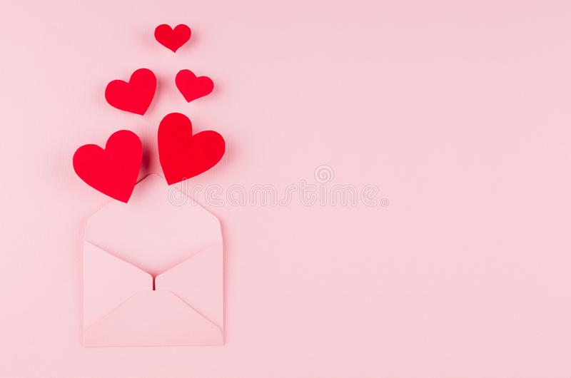 Opened paper envelope with fly out red hearts on soft pink color background. Copy space. Valentine day concept for design. Opened paper envelope with fly out stock images