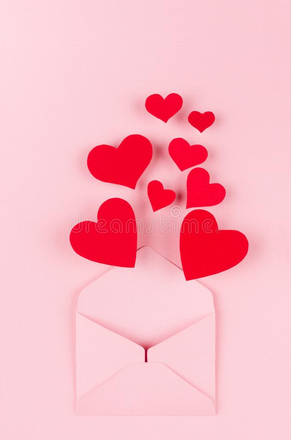 Opened paper envelope with red hearts as love message on soft pink color background. Valentine day concept for design. royalty free stock images