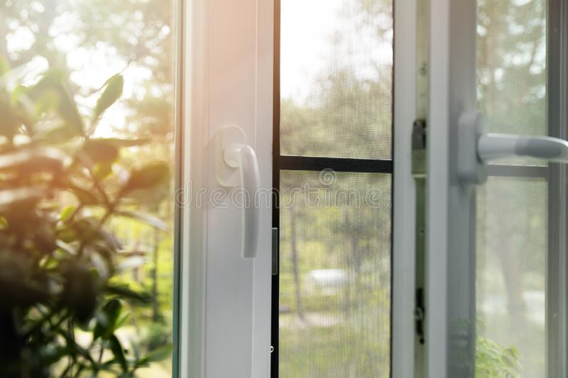 Opened plastic pvc window with mosquito net wire screen installed. Sunny summer day royalty free stock image