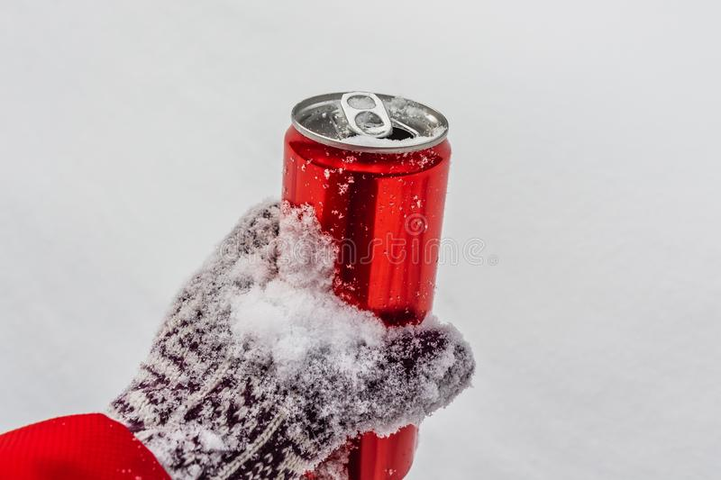 An opened red shiny bright tin can with white snow on its surface with key for cool cold soft drinks in a hand in a royalty free stock photography