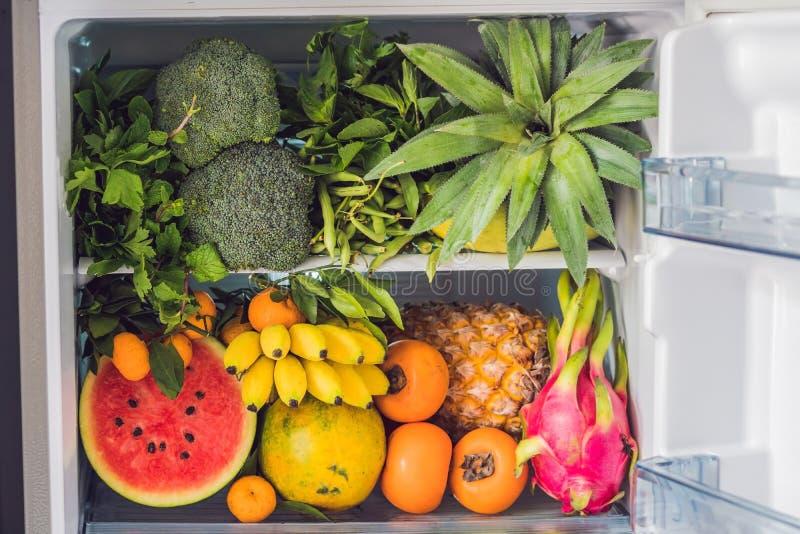 Opened refrigerator full of vegetarian healthy food, vibrant colour vegetables and fruits inside on fridge. Vegan Fridge royalty free stock photo