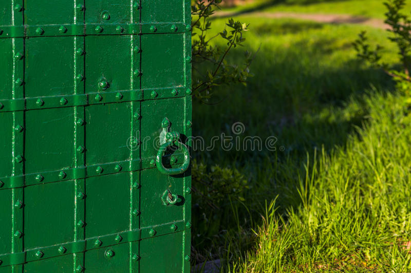 Opened riveted green door with selective focus royalty free stock image