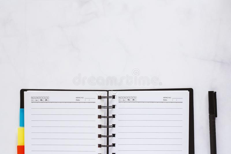 Opened spiral notebook with black pen on white marble background. For workspace concept stock photography