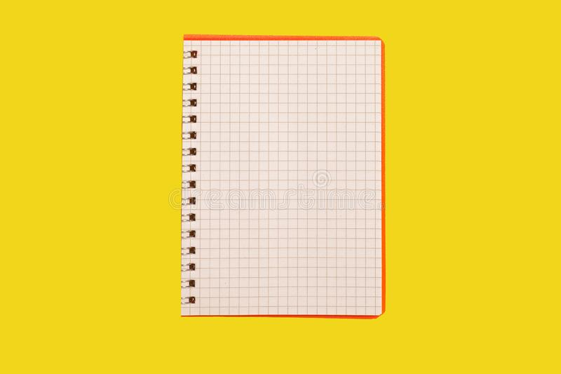 Opened spiral notebook on a yellow background. Opened spiral notebook lying on a yellow surface. concept of office stationary. free copyspace stock photography