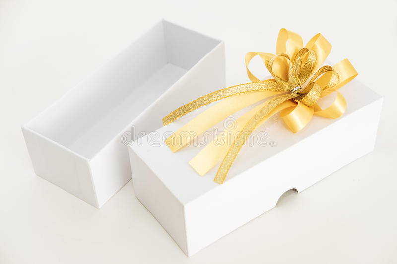 Opened square white gift box with golden ribbon, on white background stock photography