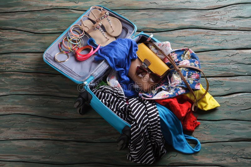 Opened suitcase with crumpled clothes. Sandals and bracelets in luggage bag. Don't break the sunglasses. Ready to travel stock photo