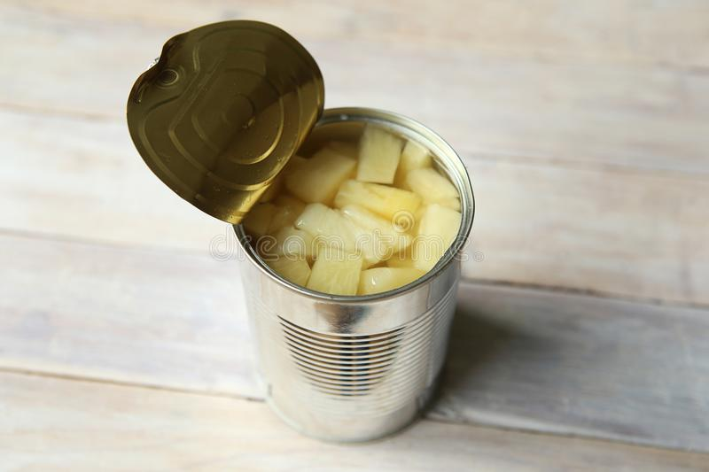 Opened tin can of canned pineapple pieces. stock photo