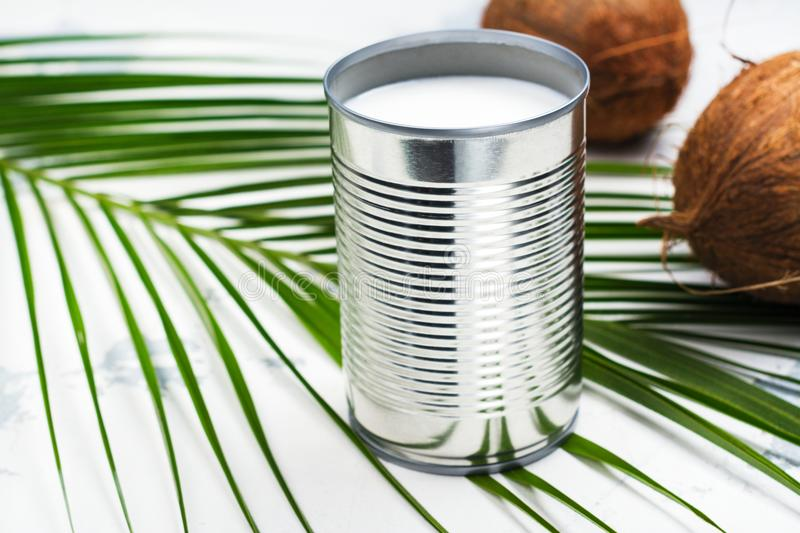 Opened tin can with coconut milk drink. Alternative non dairy vegan milk on white stone table stock images