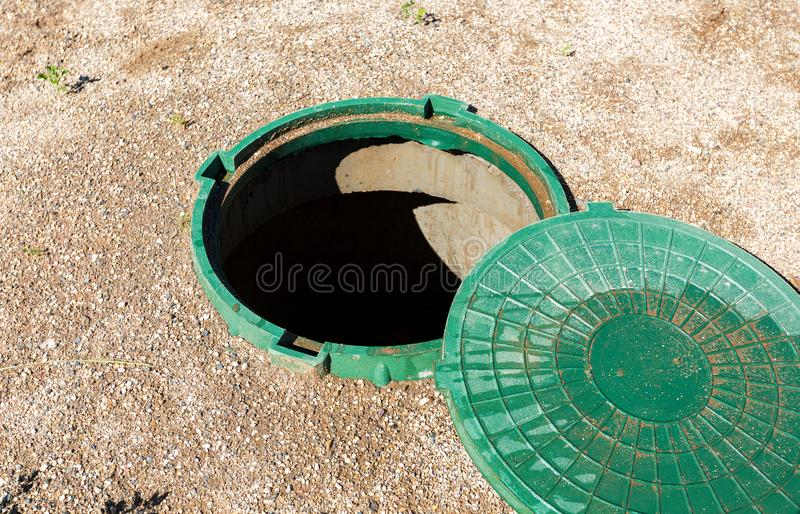 Opened unsecured sewer manhole of rural septic tank royalty free stock photo