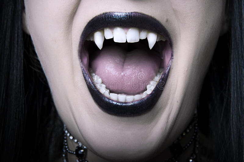 Opened vampire woman mouth closeup royalty free stock photography