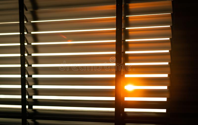 Opened venetian plastic blinds with sunlight in the morning. White plastic window with blinds. Interior design of living room. With window horizontal blinds royalty free stock photography