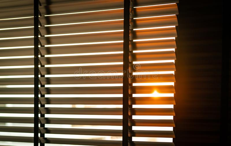 Opened venetian plastic blinds with sunlight in the morning. White plastic window with blinds. Interior design of living room royalty free stock photos