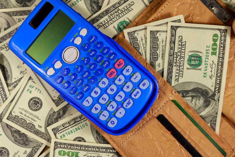 Opened wallet and calculator on american one hundred dollar bills background royalty free stock image