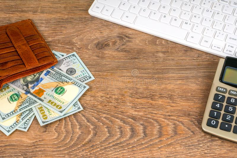 Opened wallet with dollar banknotes and calculator on table royalty free stock photography