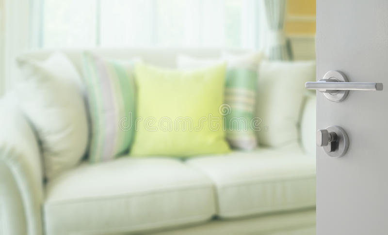 Opened white door to living room with green pillows on modern sofa royalty free stock images