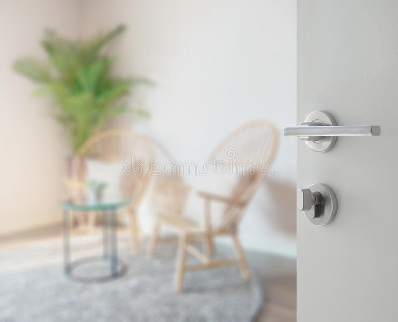 Opened white door to living room interior with wooden chair stock image