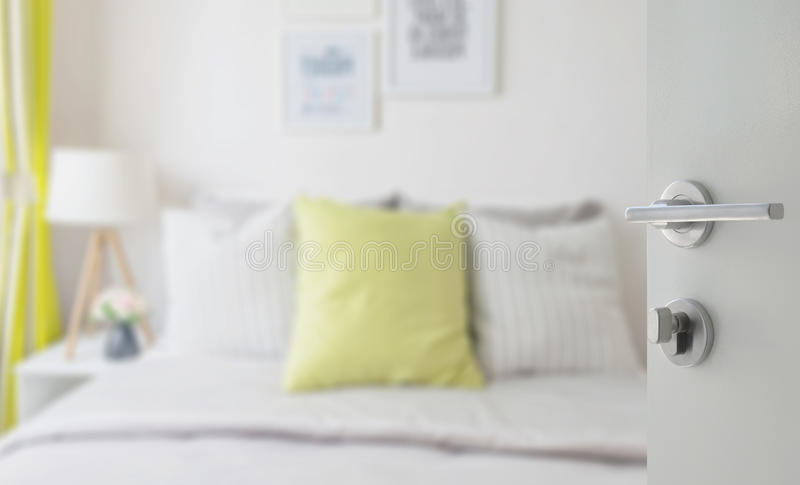 Opened white door to modern bedroom with green pillow on bed stock image