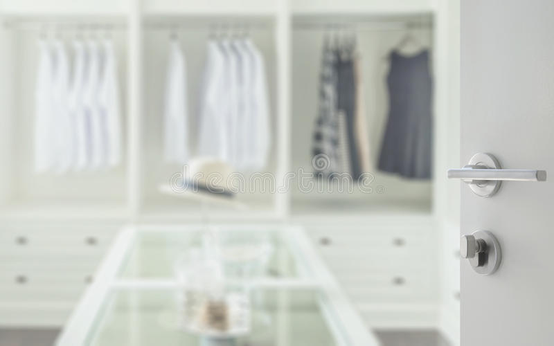 Opened white door to walk in closet room with dresser table royalty free stock photography