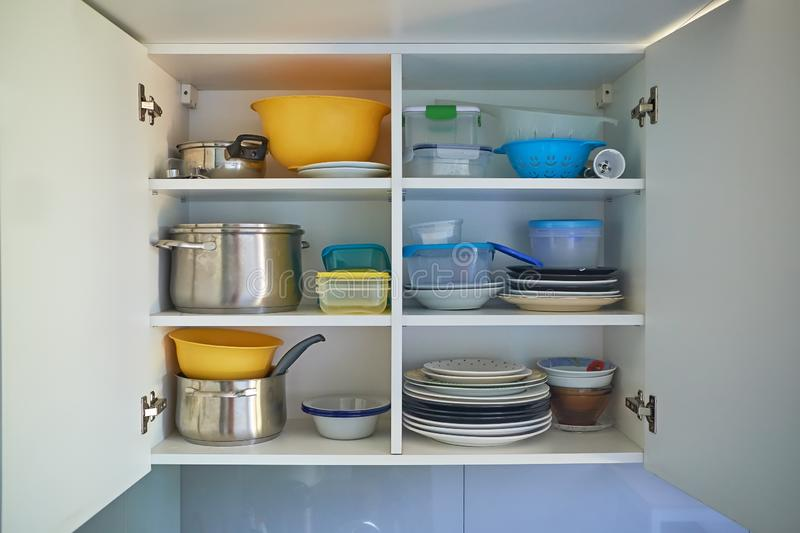 Opened white kitchen cupboard with plates, metal pots and food containers. Open white kitchen cabinet with kitchenware inside, plates, metal pots and food royalty free stock photo