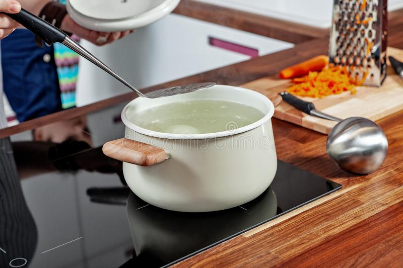 Opened white saucepan with wood pens on the black stove in the kitchen room. Cooking a soup, boiling water, mixing. Opened white saucepan with wood pens on the royalty free stock images