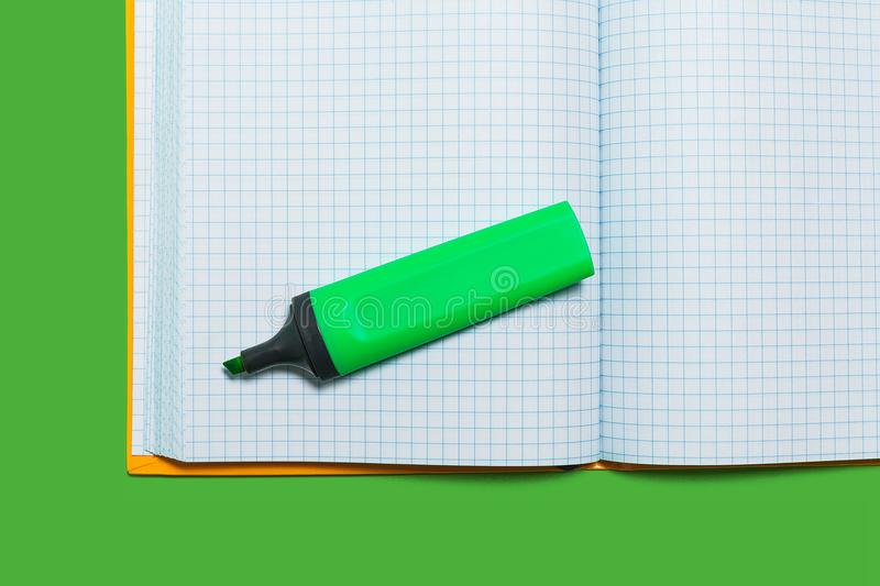 Opened workbook and a marker on a green surface. White opened workbook with marker without a cap lying on a green surface. concept of business or educational stock photography
